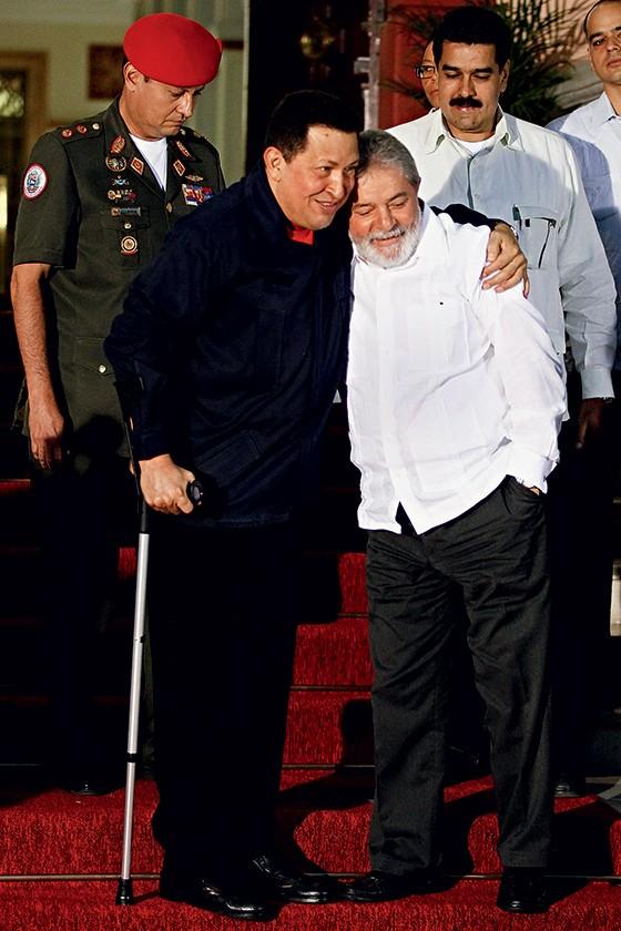 EFICIENTE Lula com Hugo Chávez em Caracas, em 2011, e trechos de seus contratos com a Odebrecht (abaixo). Após uma palestra de Lula, o governo venezuelano pagou uma dívida com a Odebrecht (Foto: Jorge Silva/Reuters)