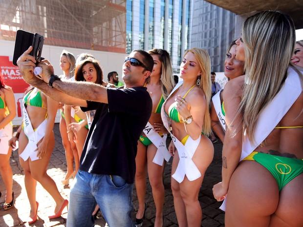 Mais um fã tira foto com as candidatas do concurso Miss Bumbum na Avenida Paulista (Foto: Paulo Whitaker/Reuters)