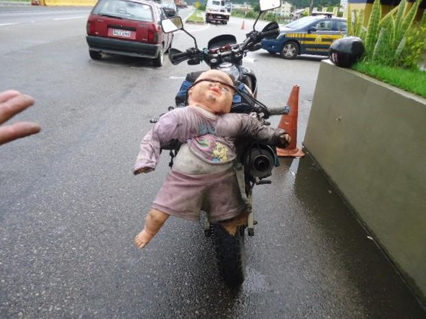 Motociclista amarrou boneca no veículo e placa ficou sem condição de visibilidade (Foto: PRF/Divulgação)
