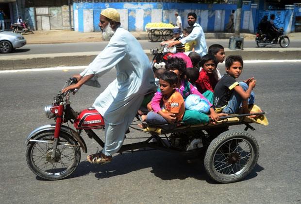 Paquistanês é visto levando ao menos 8 crianças a reboque em triciclo motorizado em rua em Karachi, no Paquistão, nesta sexta-feira (5) (Foto: Rizwan Tabassum/AFP)