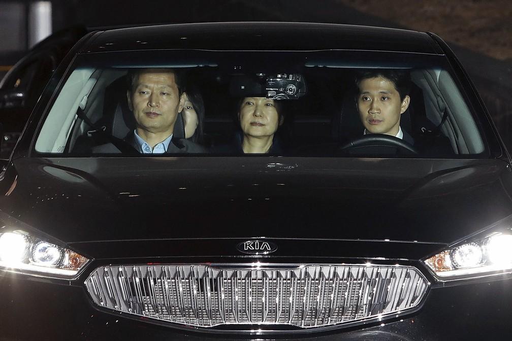 Park, ao centro, a bordo do carro em que foi levada para o centro de detenção (Foto: Chung Sung-Jun/Pool photo via AP)