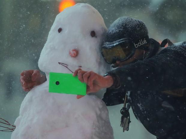 Jovem posa ao lado de boneco de neve na Times Square, em Manhattan, Nova York (Foto: Carlo Allegri/Reuters)