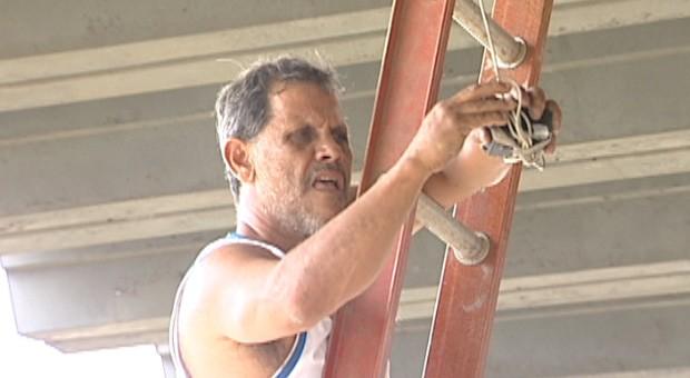 Róbson Santana, presidente da Desportiva Ferroviária, consertando o placar eletrônico do estádio Engenheiro Araripe (Foto: Reprodução/TV Gazeta)