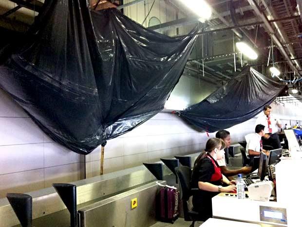 Lonas são colocadas atrás do guichê de check-in no Aeroporto JK, para evitar goteiras em esteiras (Foto: Isabella Formiga/G1)
