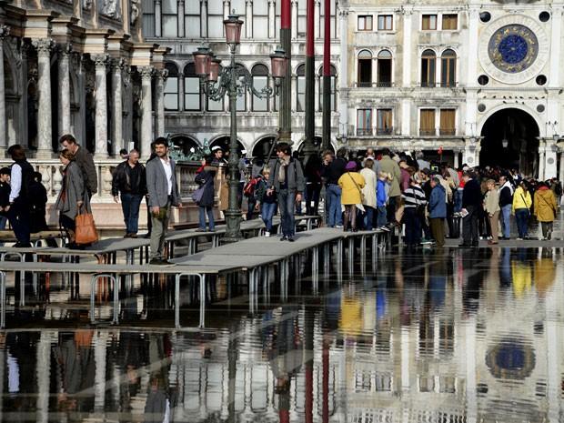 Tábuas suspensas foram colocadas para que os turistas possam se deslocar durante a inundação (Foto: Olivier Morin/AFP)
