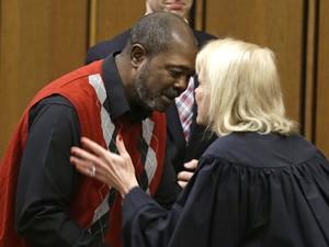 Kwame Ajamu recebe um abraço da juíza Pamela Barker após o final da sessão onde foi inocentado (Foto: AP Photo/Tony Dejak)