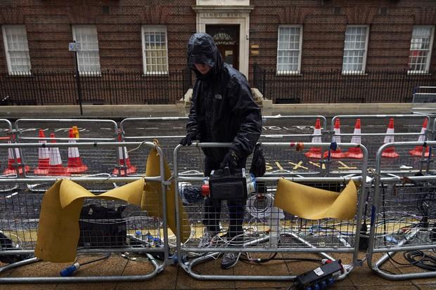 Funcionário trabalha para retirar estrutura montada para atender jornalistas na porta da maternidade (Foto: AFP)