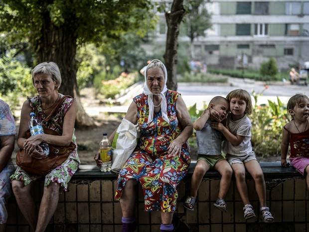 Refugiados esperam na frente de um albergue controlado por rebeldes pró-russas no centro de Donetsk, na Ucrânia (Foto: Bulent Kilic/AFP)