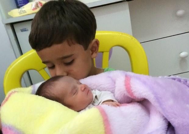 Deyvid faz carinho na irmã Isabella em Goiânia, Goiás (Foto: Paula Resende/ G1)