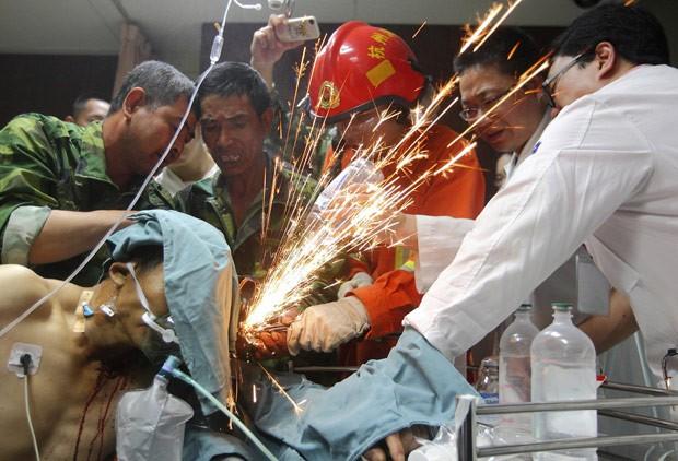 Colegas de Zheng 'limam' as varas de metal (Foto: China Daily/Reuters)