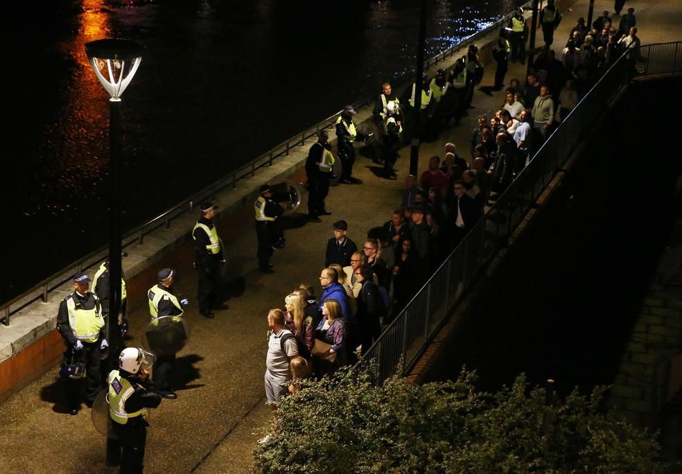 Policiais falam com pessoas que foram retiradas da London Bridge após ato terrorista deste sábado (Foto: REUTERS/Neil Hall)