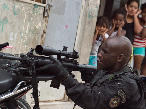 favela maré meninas assistem bope (Foto: Christophe Simon/ AFP)