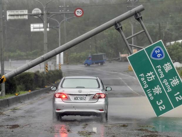 Carro passa por um sinal de trânsito derrubado pelo tufão (Foto: Sam Yeh / AFP Photo)