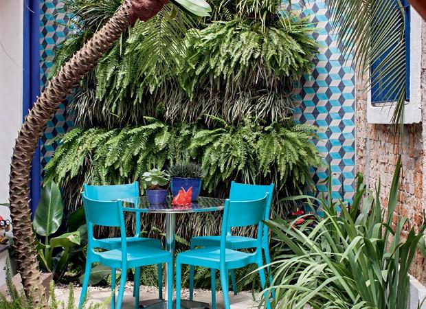Ocantinho entre a cozinha do escritório e a sala de reuniões ganhou mesa e cadeiras da Tok & Stok e um jardim vertical com samambaias e barbas-de-serpente intercaladas. Nas laterais, ladrilhos hidráulicos da Ladrilar.  (Foto: Gui Morelli/Editora Globo)