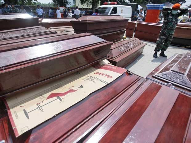 Soldado indonésio usa máscara perto de caixões utilizados para as vítimas de Hércules C-130 que caiu em Medan (Foto: Binsar Bakkara / AP Photo)