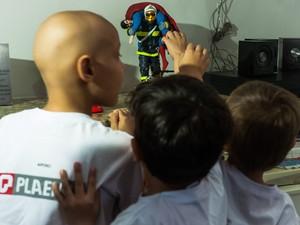 Crianças observam boneco de bombeiro salvando o personagem Superman. (Foto: Maria Anffe)
