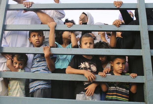 Crianças palestinas são vistas em caminhão ao deixarem suas casas durante bombardeio israelense em Khan Younis, no sul da Faixa de Gaza, nesta quarta-feira (24) (Foto: Ibraheem Abu Mustafa/Reuters)