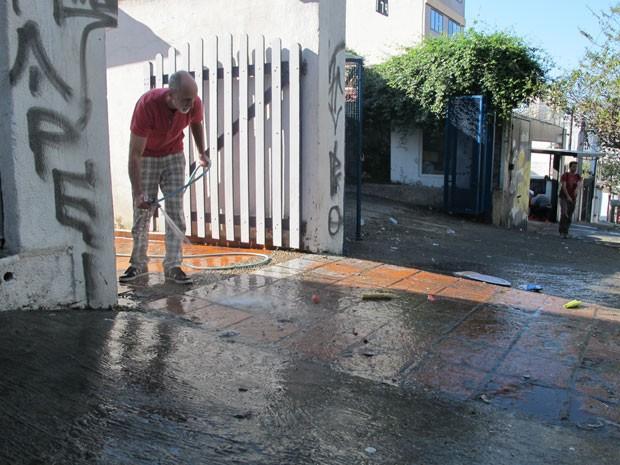 Morador limpa rua na manhã desta terça na Vila Madalena (Foto: Letícia Macedo/G1)