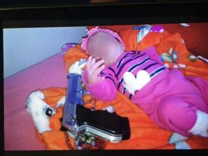 Bebê foi fotografada ao lado de arma em Balneário Piçarras (Foto: Polícia Militar/Divulgação)