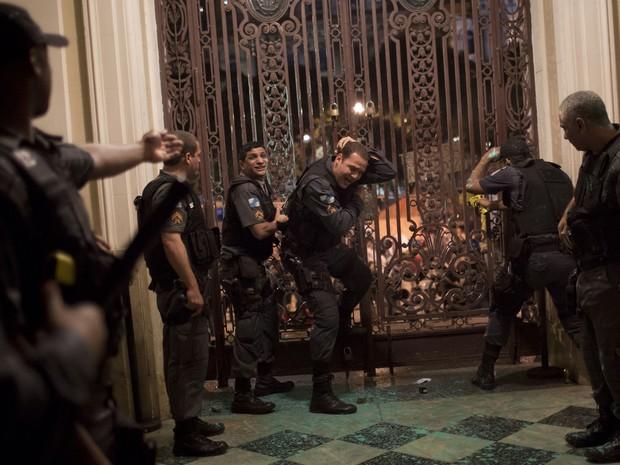 Policial, ao centro, reage após ser atingido dentro da Câmara por um objeto lançado por manifestantes. (Foto: Felipe Dana/AP)