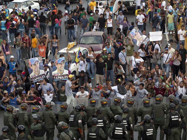 Apoiadores do candidato derrotado na eleição venezuelana enfrentam polícia durante protesto em caracas. (Foto: Ramon Espinosa/AP)