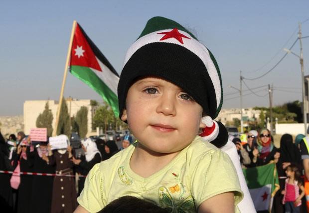 Garoto participa de protesto contra o regime do presidente sírio Bashar al Assad nesta quinta-feiras (17) em Amã, na Jordânia (Foto: AFP)
