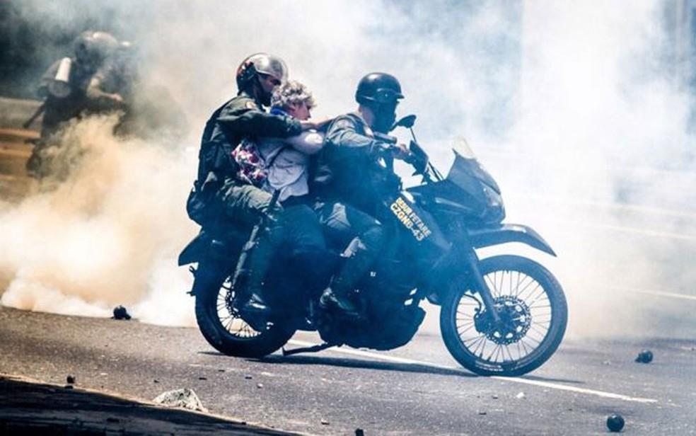 Manifestante desconhecida é levada por policiais da guarda nacional (Foto: Leo Álvarez)
