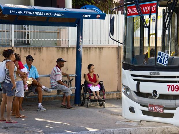 Cadeirante espera por ônibus em ponto sem estrutura (Foto: Jonathan Lins/G1)