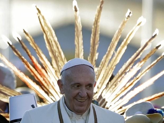 O Papa Francisco sorri em frente ao cocar de um indígena que participava da recepção do pontífice no aeroporto de El Alto, na Bolívia (Foto: Gregorio Borgia/AP)