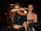 De barriga de fora, Lindsay Lohan deixa boate e tenta evitar flashes