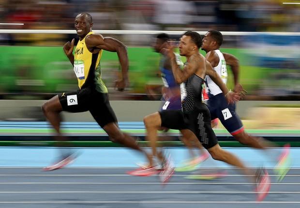 Usain Bolt sorri diante da vantagem em relação aos rivais (Foto: Cameron Spencer/Getty Images)