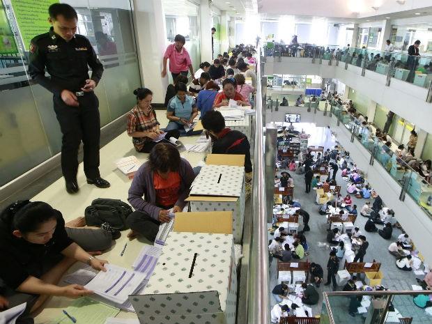 Policial observa o preparo de cédulas e urnas para as eleições gerais na Tailândia que ocorre no domingo (2) (Foto: Wason Wanichakorn/AP)