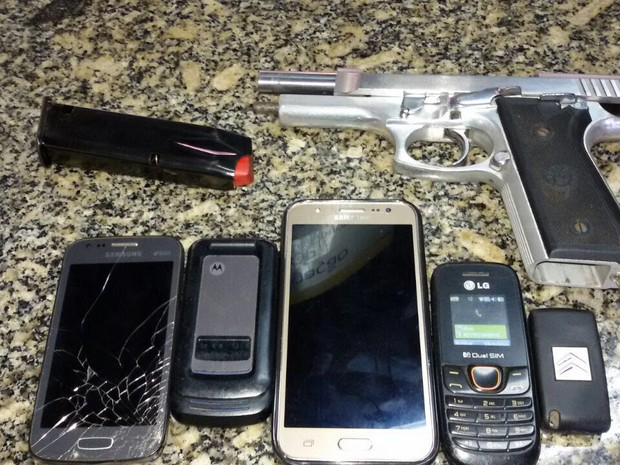 Arma e celulares apreendidos na abordagem foram levados para o 123ª DP (Foto: Polícia Militar/Divulgação)