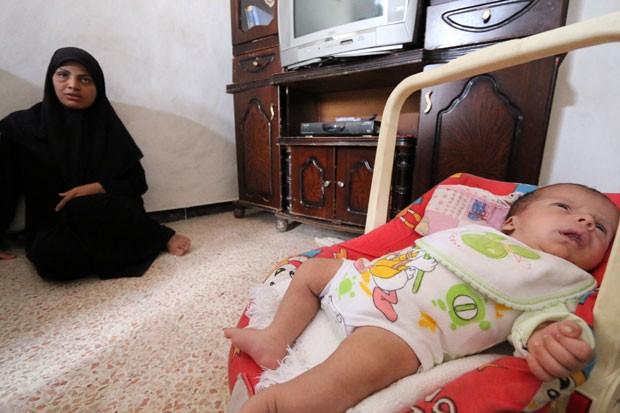 Umm Mahmud é vista ao lado de seu filho, Mahmud Idilbi, que foi resgatado dos escombros de um bombardeio na Síria (Foto: Zein Al-Rifai/AFP)