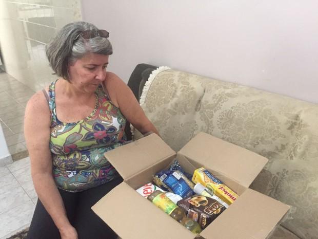 Ana Couto, servidora da saúde há 23 anos, vai usar itens de uma cesta básica que ganhou para montar sua ceia (Foto: Patrícia Teixeira)