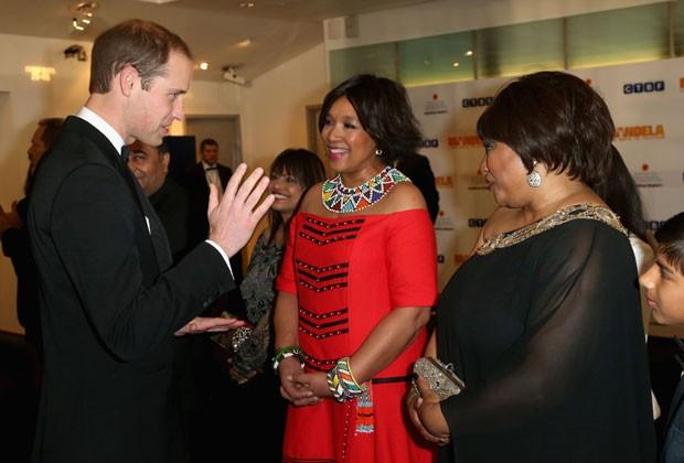O príncipe William se encontra com Zindzi Mandela, à direita, filha de Mandela, durante estreia de filme sobre o sul-africano em Londres. Ela soube da morte do pai durante a projeção (Foto: Chris Jackson/AP)