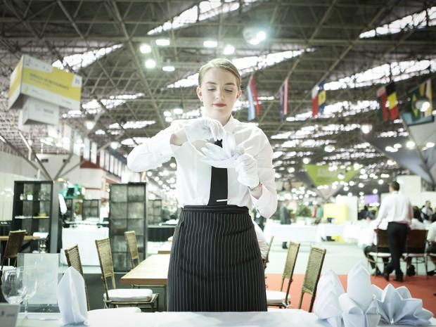 Competidora prepara mesas que vão receber os clientes na disputa de serviços de restaurante (Foto: Caio Kenji/G1)