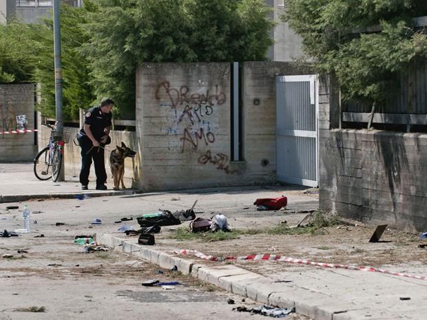 Policial com cão treinado inspeciona o local onde ocorreu a explosão  (Foto: AP)