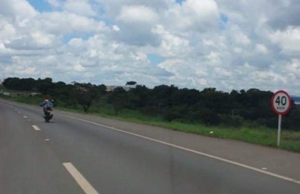Motociclista pilota deitado sobre o tanque do veículo em rodovia federal, em Goiás (Foto: Reprodução/ TV Anhanguera)