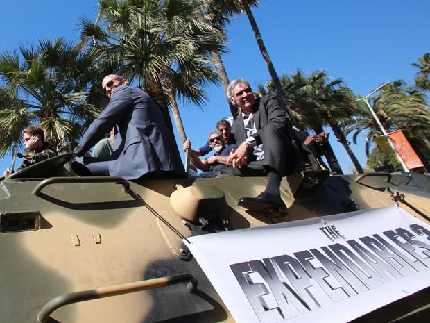 Jason Statham (2º, a partir da esquerda), Mel Gibson, Sylvester Stallone e Harrison Ford sobre tanque de guerra para divulgar 'Os mercenários 3' no Festival de Cannes (Foto: Loic Venance/AFP)
