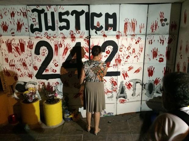 Manifestante pinta marcas de mãos em vermelho na porta de entrada da Kiss (Foto: Daniel Favero/G1)