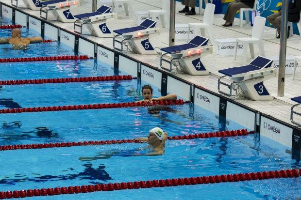Cesar Cielo permanece na piscina após chegar em 6º lugar na final dos 100 metros nado livre, enquanto seu rival, o australiano James Magnussen, medalha de prata, o observa, em Londres, dia 1º de agosto de 2012 (Foto: Mauricio Lima/ÉPOCA)