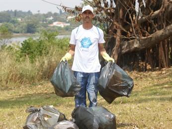 Roney Santana trabalhando na limpeza da margem do lago (Foto: Vianey Bentes)