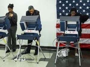 Ao lado de duas eleitoras, Barack Obama vota antecipadamente no Dr. Martin Luther King Community Service Center, em Chicago, Illinois, na segunda-feira (20) (Foto: AFP Photo/Brendan Smialowski)