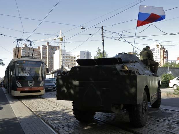 Rebeldes pró-Rússia em veículo blindado se deslocam perto de complexo ocupado do Ministério do Interior em Donetsk nesta terça (1º) (Foto: Foto AP/Dmitry Lovetsky)