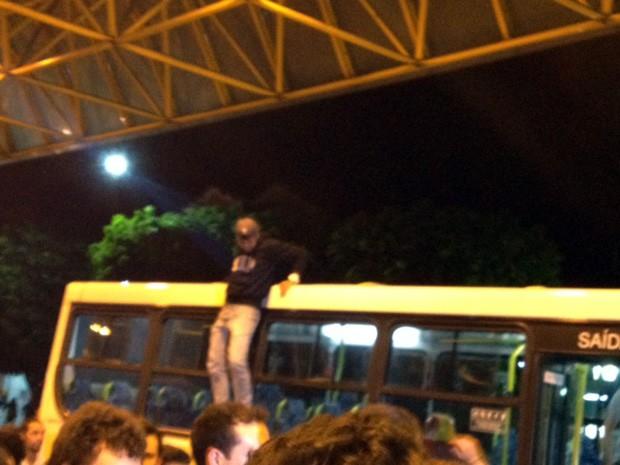 Manifestante se pendura em janela de ônibus e é retirado pelos próprios manifestantes (Foto: Jéssica Balbino / G1)