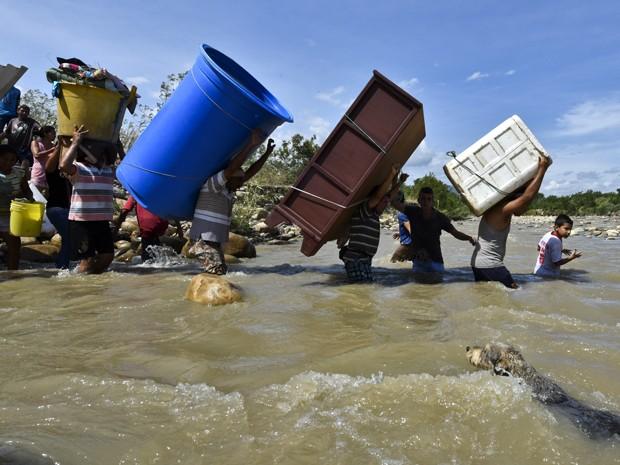 Colombianos deportados da Venezuela carregam móveis e outros objetos através do rio Tachira, na fronteira entre os dois países, na terça (25) (Foto: AFP Photo/Luis Acosta)