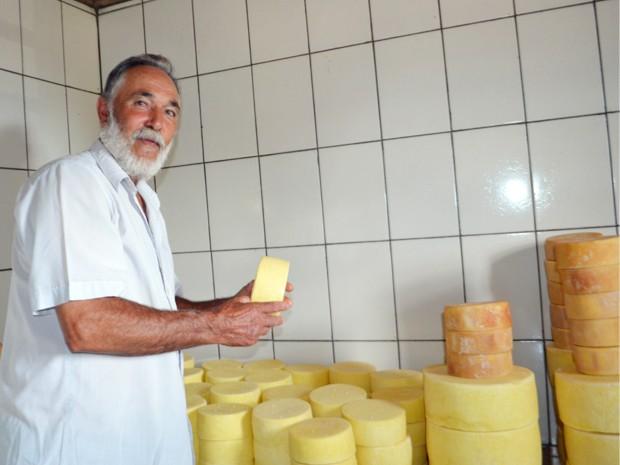 Seu Jair Barros segura queijo parmesão produzido em na pequena fábrica em Alagoa, MG (Foto: Samantha Silva / G1)