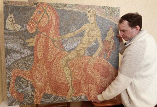 Artista Igor Arinich contou que usa entre 500 e 3 mil cédulas em cada obra. (Foto: Vasily Fedosenko/Reuters)