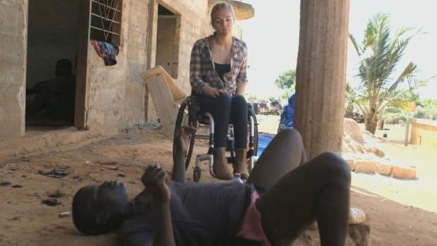 """Grace está no chão e recebeu """"remédio"""" num chamado campo de cura; Sophie Morgan visitou Gana para conhecer condições de deficiente físicos no país' (Foto: BBC)"""